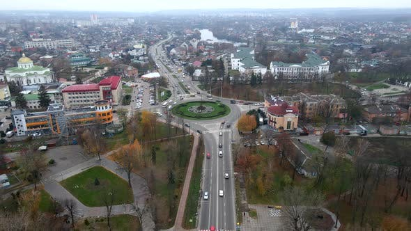 Thumbnail for Aerial View of Roundabout Road with Circular Cars in Small European City at Cloudy Autumn Day