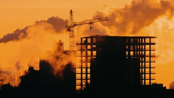 Thumbnail for Construction Site Tower Crane Building in the City, Sunrise or Sunset Golden Hour Backlit Silhouette