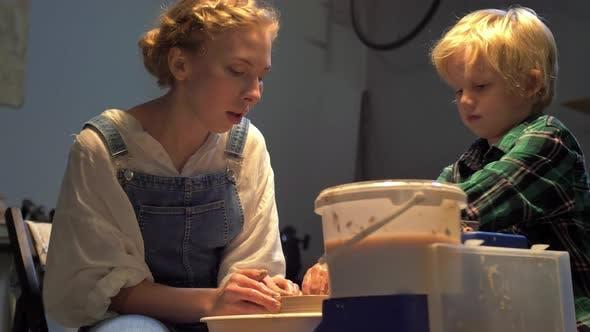 Thumbnail for Frau und Junge machen Topf auf Keramik Rad in Werkstatt