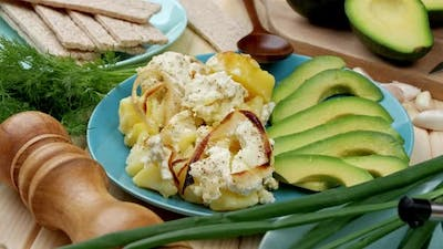 Baked Casserole with Potatoes and Cheese Avocado Slices Close Up