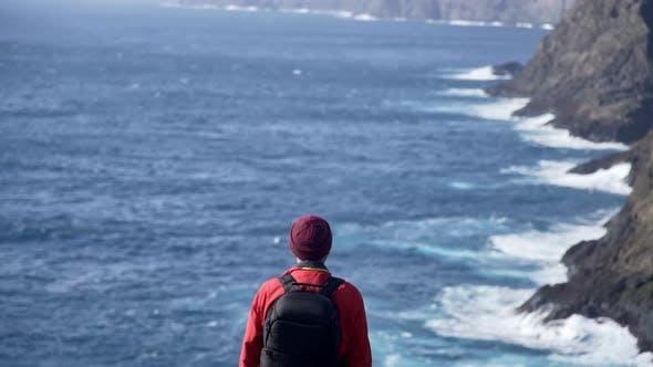 Man Overlooking Dramatic Coastline