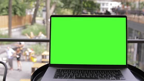 Thumbnail for Mock-up Green Screen Laptop MacBook Pro Standing on the Desk in the Modern Co-working park