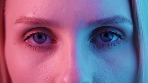 Female Blue Eyes in Neon Light Closeup