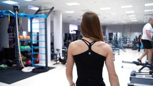 Femme athlétique avec son dos va au simulateur dans le gymnase