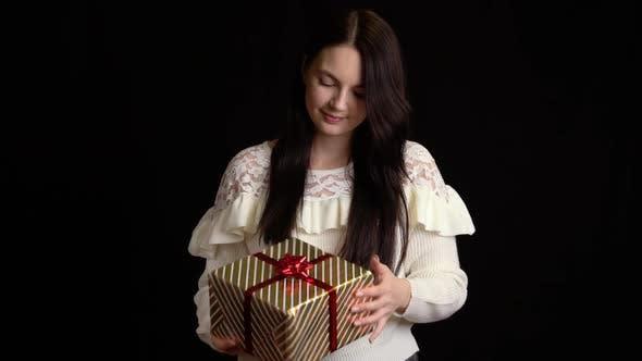 Thumbnail for Junge Frau mit einer Geschenkbox auf schwarzem Hintergrund. Geschenkbox mit weißem Band für ein glückliches neues Jahr