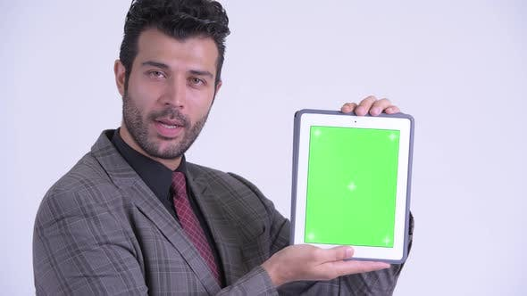 Thumbnail for Face of Happy Bearded Persian Businessman Showing Digital Tablet