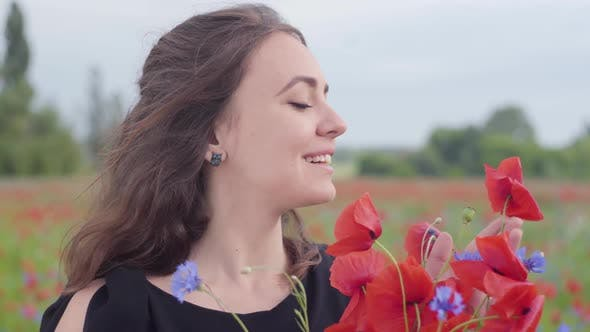 Thumbnail for Portrait of a Pretty Girl in a Poppy Field Sniffing Bouquet of Flowers