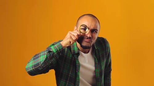 Young African American Man Looking Through Magnifying Glass Against Yellow Background