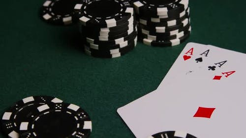 Rotating shot of poker cards and poker chips on a green felt surface - POKER 007