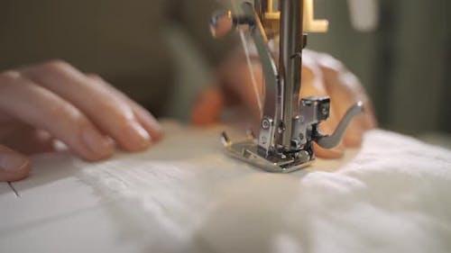 A Female Hand Pushes Material Through a Sewing Machine
