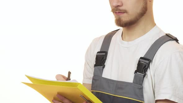 Thumbnail for Cropped Shot of a Industry Worker Smiling Making Notes on Clipboard