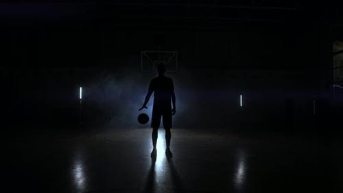 Basketball Player Knocks the Ball in the Light of the Lamps Shining Behind Stands in the Duma and