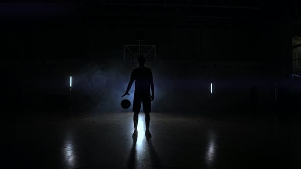 Thumbnail for Basketball Player Knocks the Ball in the Light of the Lamps Shining Behind Stands in the Duma and