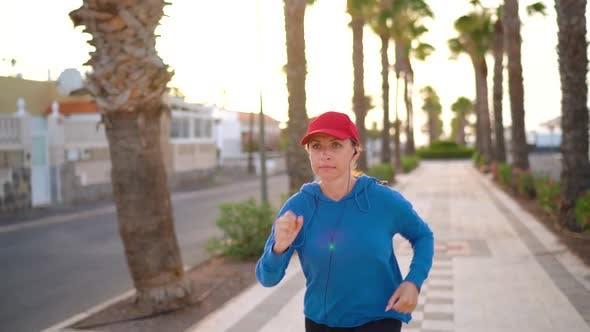 Thumbnail for Woman with Headphones Runs Down the Street Along the Palm Avenue at Sunset, Healthy Active Lifestyle