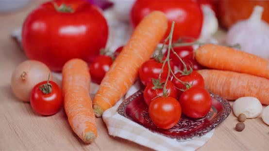 Thumbnail for Close Up of Various Vegetables on Table Rotating. Fresh Cherry Tomatos, Carrot, Red Onion and Garlic