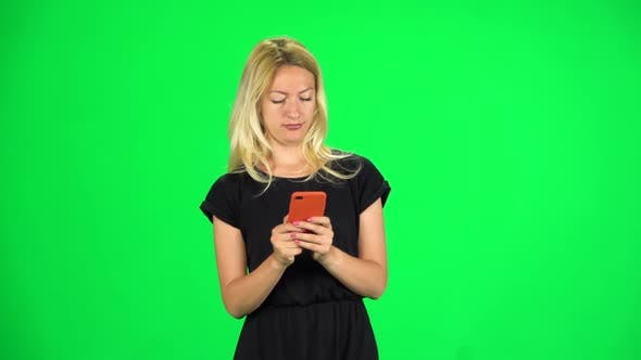Thumbnail for Blonde Girl Goes and Texting with Smartphone on Green Screen at Studio. Slow Motion