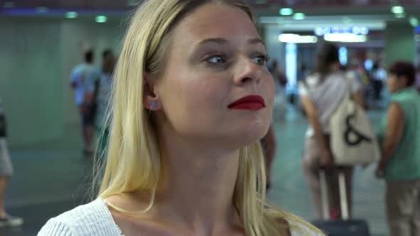 Thumbnail for A Young Beautiful Woman Looks Around in a Train Station Building - Face Closeup