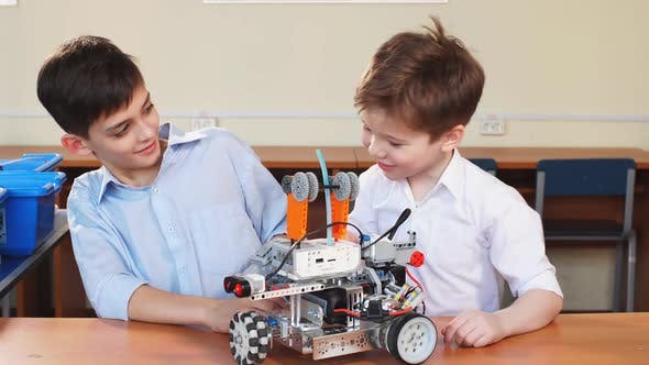 Thumbnail for Two Brothers Kids Playing with Robot Toy at School Robotics Class, Indoor.