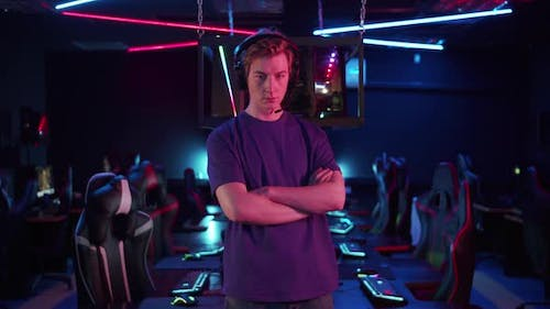 Before the Start of the Cyber Tournament a Young Player Poses Against the Background of His Teams