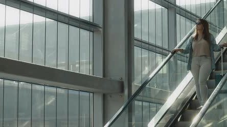 Woman going down escalator holding her suitcase, slow motion BMPCC 4K
