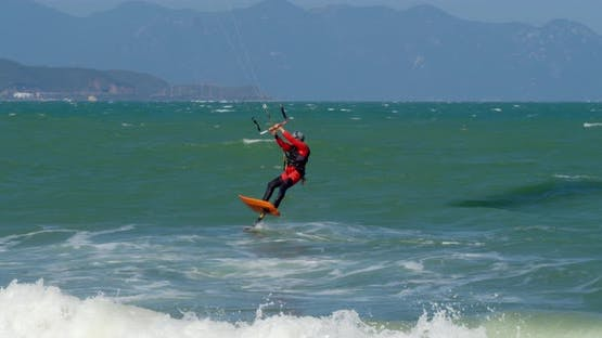 Athlete Showing Sport Trick Jumping with Kite and Board in Air
