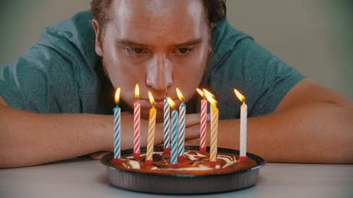 Sad Man Is Blowing Out the Candles on the Birthday Cake