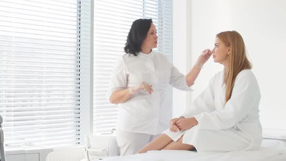Thumbnail for Female Cosmetologist Doing Facial Laser Treatment To a Female Client