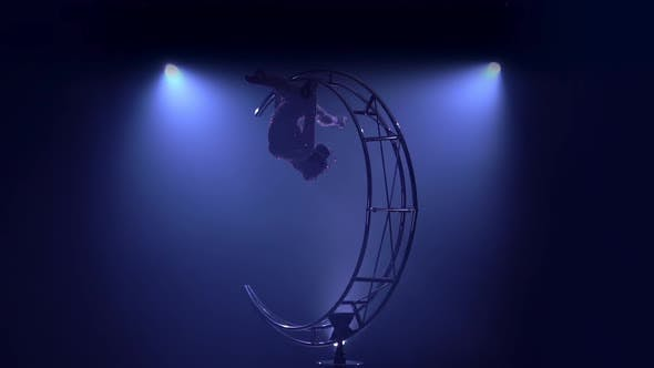 Thumbnail for Gymnast Hangs Upside Down in a Twine on a Rotating Structure Moon. Blue Smoke Background. Slow