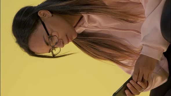 Close-up of Black Woman in Eyeglasses Working on Smartphone.