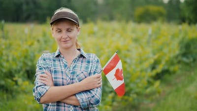 Woman Farmer with Canadian Flag Looking at the Camera