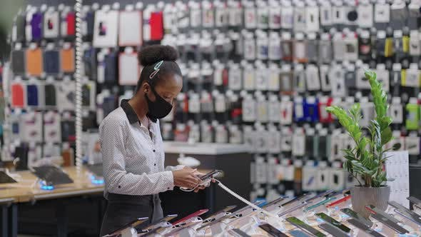 Afroamerican Female Shopper is Choosing Mobile Phone in Electronics Shop During Pandemic of Covid19