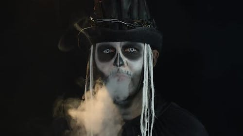 Frightening Man in Creepy Skeleton Halloween Cosplay Exhaling Cigarette Smoke From His Mouth