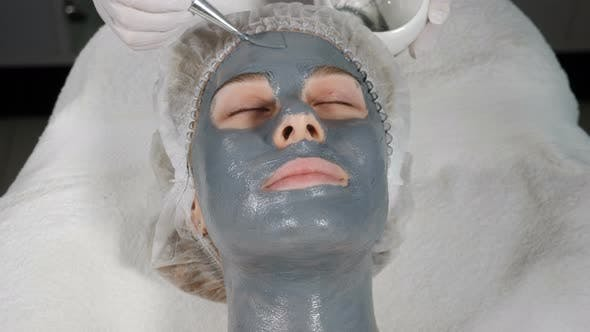Top View of Female Client Getting Facial Beauty Treatment. Applying Facial Mask To Face Skin at