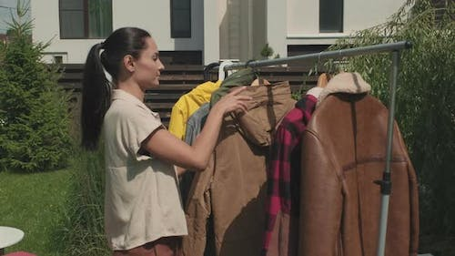 Woman Looking at Second Hand Clothes at Garage Sale