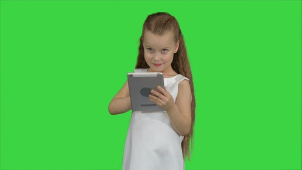 Thumbnail for Small Girl Using Tablet Computer on a Green Screen, Chroma Key
