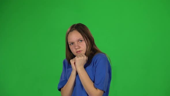 Thumbnail for Teen Girl Is Scared and Hiding Her Face in Studio on Green Background.