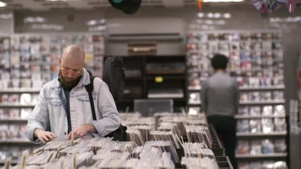 Thumbnail for Caucasian Musician with Guitar Browsing through Vinyls in Record Shop