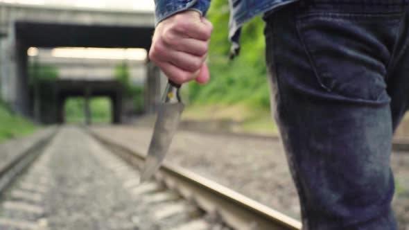 Maniac mit einem Messer in der Nähe der Bahngleise.