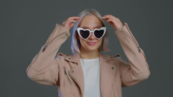 Beautiful Trendy Woman with Blonde Hair in Heart Shaped Sunglasses on Grey