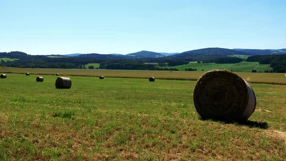 Thumbnail for Field in Countryside with Haystack - Forests in Background - Sunny Day