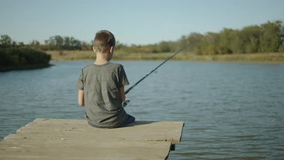 Thumbnail for Small Boy Fisherman, Catching a Fish on a Rod on the Lake. Outdoors