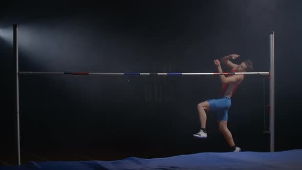 A Male Athlete Runs and Jumps High Over the Crossbar. Slow-motion Shooting of the High Jump