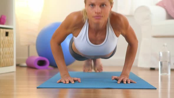 Cover Image for Healthy woman doing push ups and looking at camera