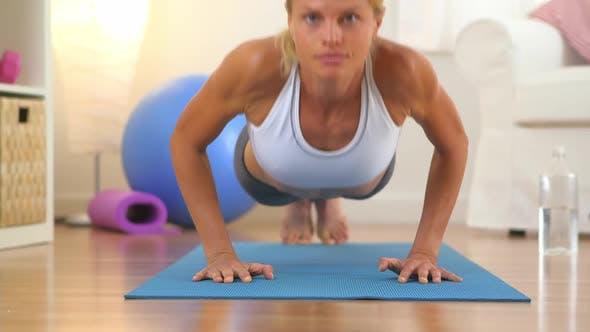 Thumbnail for Healthy woman doing push ups and looking at camera