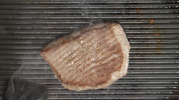 Thumbnail for Cook Inverts A Beef Steak On A Grill