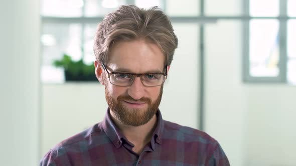Cover Image for Portrait a Smiling Bearded Guy with Glasses in a Daily Plaid Shirt Standing in the Office Center