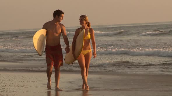 Thumbnail for Young couple walking out of waves with surfboards