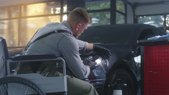 Mechaniker auf Rollstuhl Anwendung Film auf Autoscheinwerfer