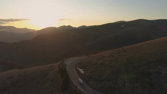 Thumbnail for White Transportation Van Driving on Mountain Road in the Evening. Last Sunbeams Shining Over