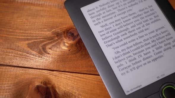 The Electronic Book Lies on a Wooden Table. Screen of Electronic Ink Displays Text of the Book